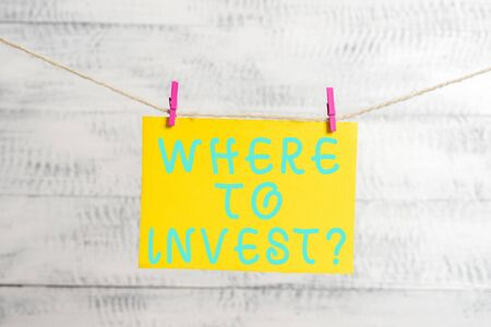Conceptual hand writing showing Where To Invest question. Concept meaning asking about actions or process of making more money Clothespin rectangle shaped paper reminder white wood desk