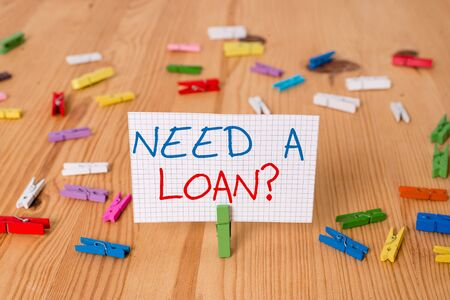 Text sign showing Need A Loan question. Business photo text amount of money that is borrowed often from bank Colored clothespin papers empty reminder wooden floor background office