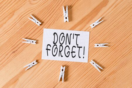 Conceptual hand writing showing Don T Forget. Concept meaning used to remind someone about important fact or detail Colored crumpled papers wooden floor background clothespin