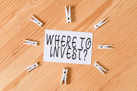 Conceptual hand writing showing Where To Invest Question. Concept meaning asking about where put money into financial schemes or shares Colored crumpled papers wooden floor background clothespin