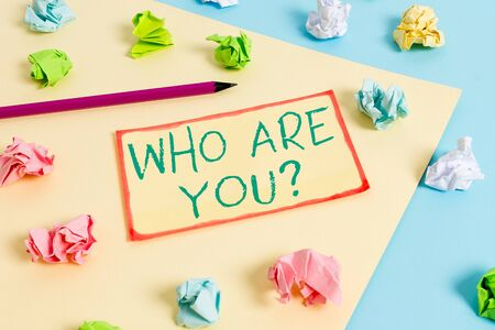 Writing note showing Who Are You question. Business concept for asking demonstrating identity or demonstratingal information Colored crumpled papers empty reminder blue yellow clothespin