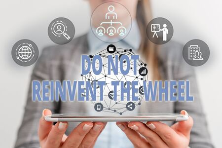 Writing note showing Do Not Reinvent The Wheel. Business concept for stop duplicating a basic method previously done Female human wear formal work suit presenting smart device