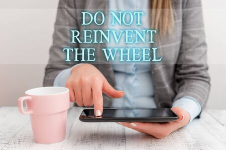 Handwriting text writing Do Not Reinvent The Wheel. Conceptual photo stop duplicating a basic method previously done Business woman sitting with mobile phone and cup of coffee on the table