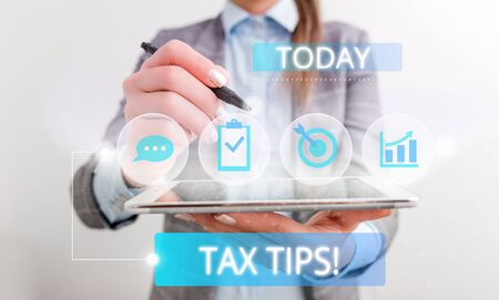 Conceptual hand writing showing Tax Tips. Concept meaning compulsory contribution to state revenue levied by government Female human wear formal work suit presenting smart device