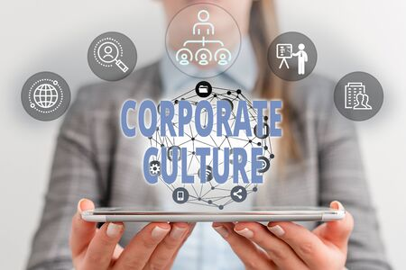 Writing note showing Corporate Culture. Business concept for pervasive values and attitudes that characterize a company Female human wear formal work suit presenting smart device Stock Photo
