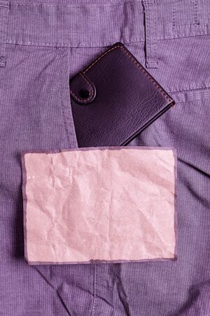Small little wallet inside man trousers front pocket near notation paper