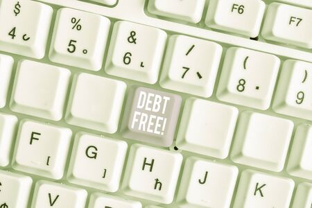 Word writing text Debt Free. Business photo showcasing does not owning any money or things to any individual or companies White pc keyboard with empty note paper above white background key copy space