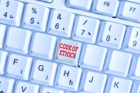 Conceptual hand writing showing Code Of Ethics. Concept meaning basic guide for professional conduct and imposes duties White pc keyboard with note paper above the white background