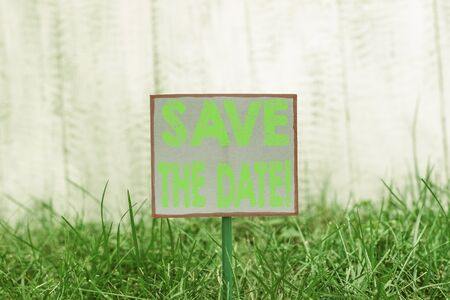 Text sign showing Save The Date. Business photo text remember not schedule anything else on this day Plain empty paper attached to a stick and placed in the green grassy land