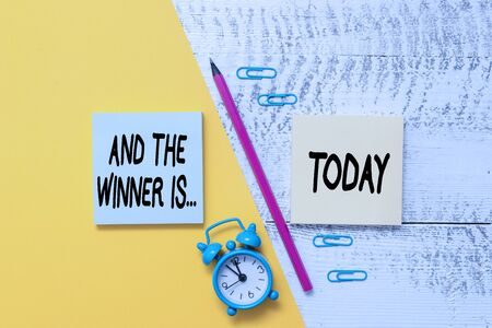 Word writing text And The Winner Is. Business photo showcasing announcing a demonstrating or thing that wins something Notepads marker pen colored paper sheet alarm clock wooden background Foto de archivo - 129365247
