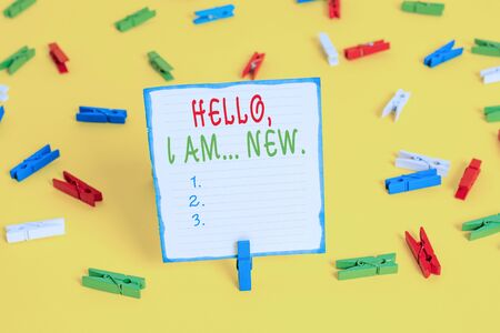 Handwriting text Hello I Am New. Conceptual photo introducing oneself in a group as fresh worker or student Colored clothespin papers empty reminder yellow floor background office
