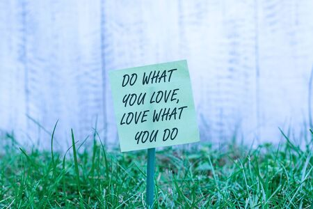 Word writing text Do What You Love Love What You Do. Business photo showcasing Pursue your dreams or passions in life Plain empty paper attached to a stick and placed in the green grassy land