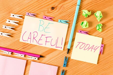 Handwriting text writing Be Careful. Conceptual photo making sure of avoiding potential danger mishap or harm Colored clothespin papers empty reminder wooden floor background office 스톡 콘텐츠