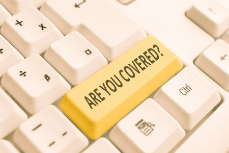 Conceptual hand writing showing Are You Covered Question. Concept meaning asking showing if they had insurance in work or life White pc keyboard with note paper above the white background Stock Photo