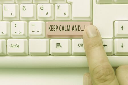 Text sign showing Keep Calm And. Business photo showcasing motivational poster produced by British government White pc keyboard with empty note paper above white background key copy space