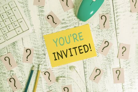 Writing note showing You Re Invited. Business concept for make a polite friendly request to someone go somewhere Writing tools and scribbled paper on top of the wooden table
