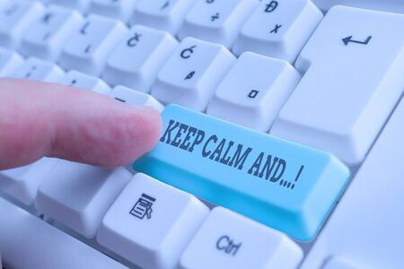 Conceptual hand writing showing Keep Calm And. Concept meaning motivational poster produced by British government White pc keyboard with note paper above the white background