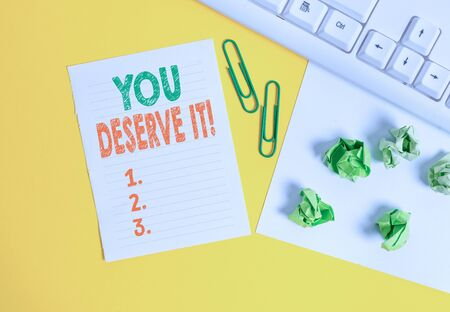Conceptual hand writing showing You Deserve It. Concept meaning should have it because of their qualities or actions Flat lay with copy space white paper with paper clips on the table