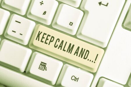 Handwriting text Keep Calm And. Conceptual photo motivational poster produced by British government White pc keyboard with empty note paper above white background key copy space