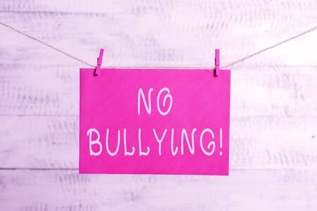 Word writing text No Bullying. Business photo showcasing stop aggressive behavior among children power imbalance Clothesline clothespin rectangle shaped paper reminder white wood desk