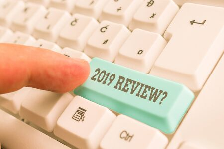 Conceptual hand writing showing 2019 Review Question. Concept meaning remembering past year events main actions or good shows White pc keyboard with note paper above the white background