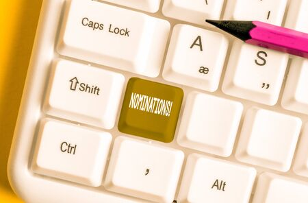 Writing note showing Nominations. Business concept for action of nominating or state being nominated for prize White pc keyboard with note paper above the white background Stock Photo