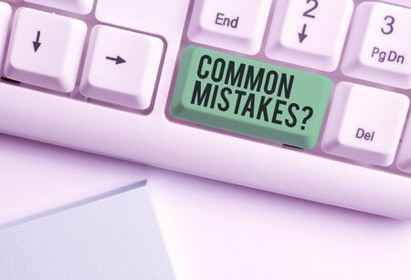 Conceptual hand writing showing Common Mistakes question. Concept meaning repeat act or judgement misguided or wrong White pc keyboard with note paper above the white background 版權商用圖片