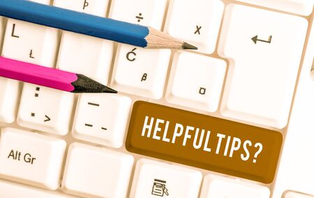 Conceptual hand writing showing Helpful Tips Question. Concept meaning secret information or advice given to be helpful knowledge White pc keyboard with note paper above the white background