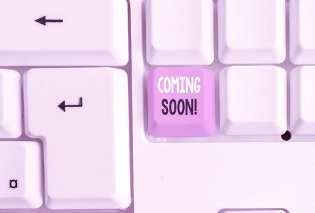 Text sign showing Coming Soon. Business photo showcasing event or action that will happen after really short time White pc keyboard with empty note paper above white background key copy space Stock Photo