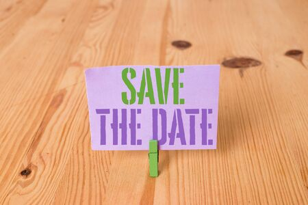 Writing note showing Save The Date question. Business concept for asking someone to remember specific day or time Wooden floor background green clothespin groove slot office