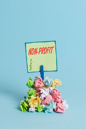 Conceptual hand writing showing Non Profit. Concept meaning type of organization that does not earn profits for its owners Reminder pile colored crumpled paper clothespin wooden space