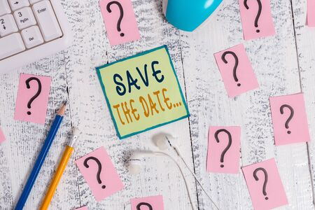 Text sign showing Save The Date. Business photo showcasing Organizing events well make day special event organizers Writing tools, computer stuff and scribbled paper on top of wooden table Stockfoto