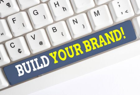 Conceptual hand writing showing Build Your Brand. Concept meaning creates or improves customers knowledge and opinions of product White pc keyboard with note paper above the white background