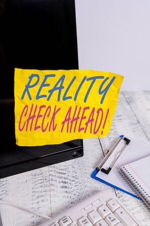 Conceptual hand writing showing Reality Check Ahead. Concept meaning makes them recognize truth about situations or difficulties Note paper taped to black screen near keyboard stationary Stock Photo