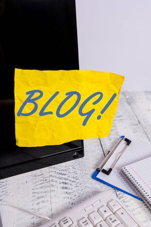 Conceptual hand writing showing Blog. Concept meaning regularly updated website web page run by individual or group Note paper taped to black screen near keyboard stationary