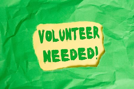 Writing note showing Volunteer Needed. Business concept for need work for organization without being paid Green crumpled colored paper sheet torn colorful background