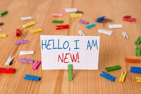 Text sign showing Hello I Am New. Business photo text used as greeting or to begin telephone conversation Colored clothespin papers empty reminder wooden floor background office Banco de Imagens