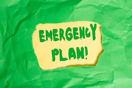 Writing note showing Emergency Plan. Business concept for actions developed to mitigate damage of potential events Green crumpled colored paper sheet torn colorful background
