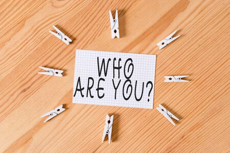 Conceptual hand writing showing Who Are You Question. Concept meaning asking about someone identity or demonstratingal information Colored crumpled papers wooden floor background clothespin