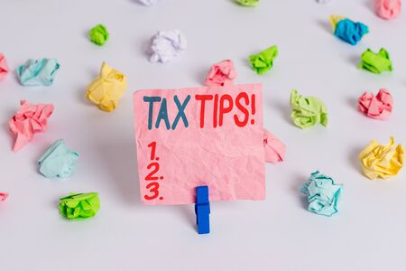 Conceptual hand writing showing Tax Tips. Concept meaning compulsory contribution to state revenue levied by government Colored crumpled paper empty reminder white floor clothespin Stock fotó