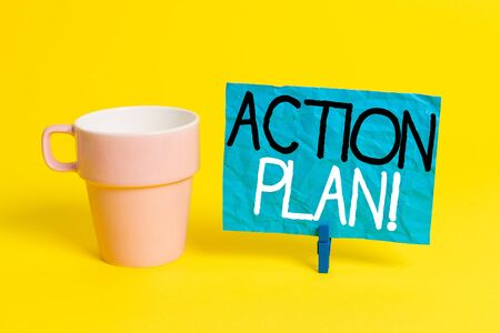 Handwriting text Action Plan. Conceptual photo proposed strategy or course of actions for certain time Cup empty paper blue clothespin rectangle shaped reminder yellow office