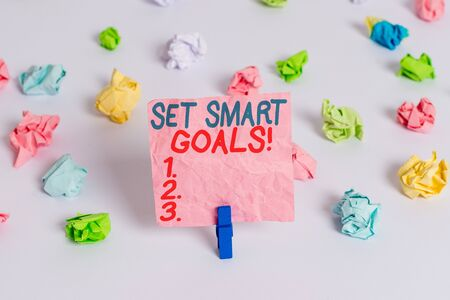 Conceptual hand writing showing Set Smart Goals. Concept meaning list to clarify your ideas focus efforts use time wisely Colored crumpled paper empty reminder white floor clothespin