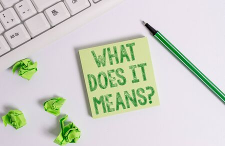 Conceptual hand writing showing What Does It Means question. Concept meaning asking someone about meaning something said and you do not understand Green note paper with pencil on white background and pc keyboard