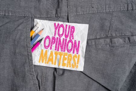 Text sign showing Your Opinion Matters. Business photo showcasing show you do not agree with something that just been said Writing equipment and white note paper inside pocket of man work trousers