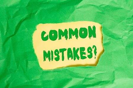 Writing note showing Common Mistakes question. Business concept for repeat act or judgement misguided or wrong Green crumpled colored paper sheet torn colorful background