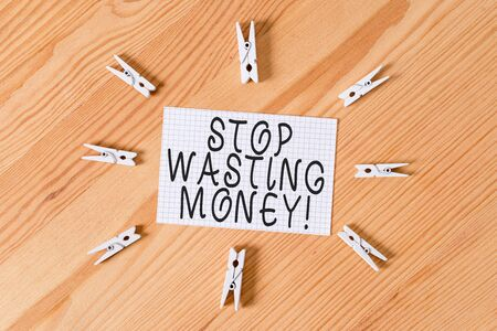 Conceptual hand writing showing Stop Wasting Money. Concept meaning advicing demonstrating or group to start saving and use it wisely Colored crumpled papers wooden floor background clothespin Archivio Fotografico
