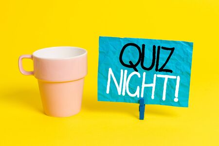Handwriting text Quiz Night. Conceptual photo evening test knowledge competition between individuals Cup empty paper blue clothespin rectangle shaped reminder yellow office