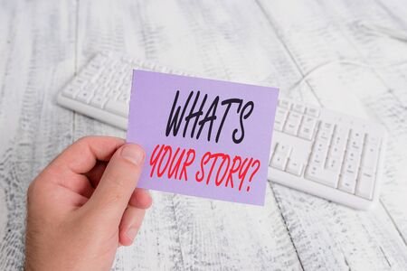 Text sign showing What S Your Story Question. Business photo showcasing asking demonstrating about his past life actions career or events man holding colorful reminder square shaped paper white keyboard wood floor