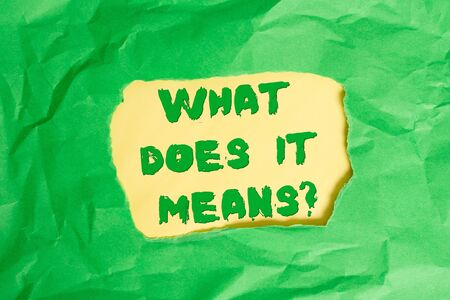 Writing note showing What Does It Means question. Business concept for asking someone about meaning something said and you do not understand Green crumpled colored paper sheet torn colorful background