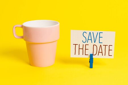 Word writing text Save The Date question. Business photo showcasing asking someone to remember specific day or time Cup empty paper blue clothespin rectangle shaped reminder yellow office